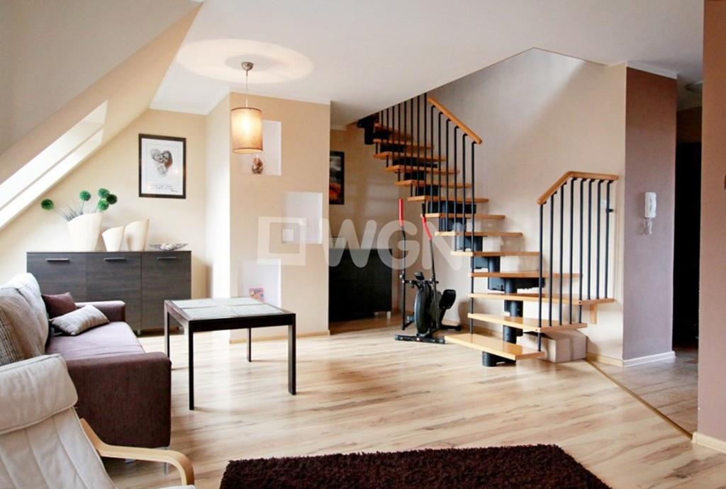 zdjęcie przedstawia salon z wejściem na drugi poziom w apartamencie do sprzedaży w Szczecinie