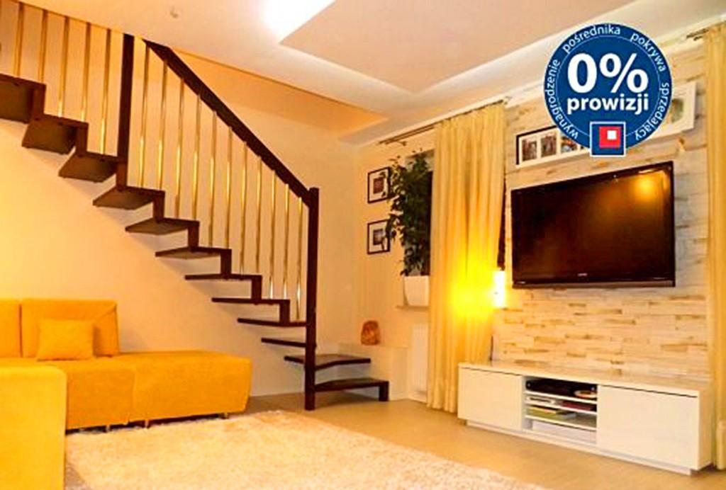 zdjęcie przedstawia fragment salonu ze sprzętem rtv i schodzami na drugi poziom w apartamencie do sprzedaży w Lublinie