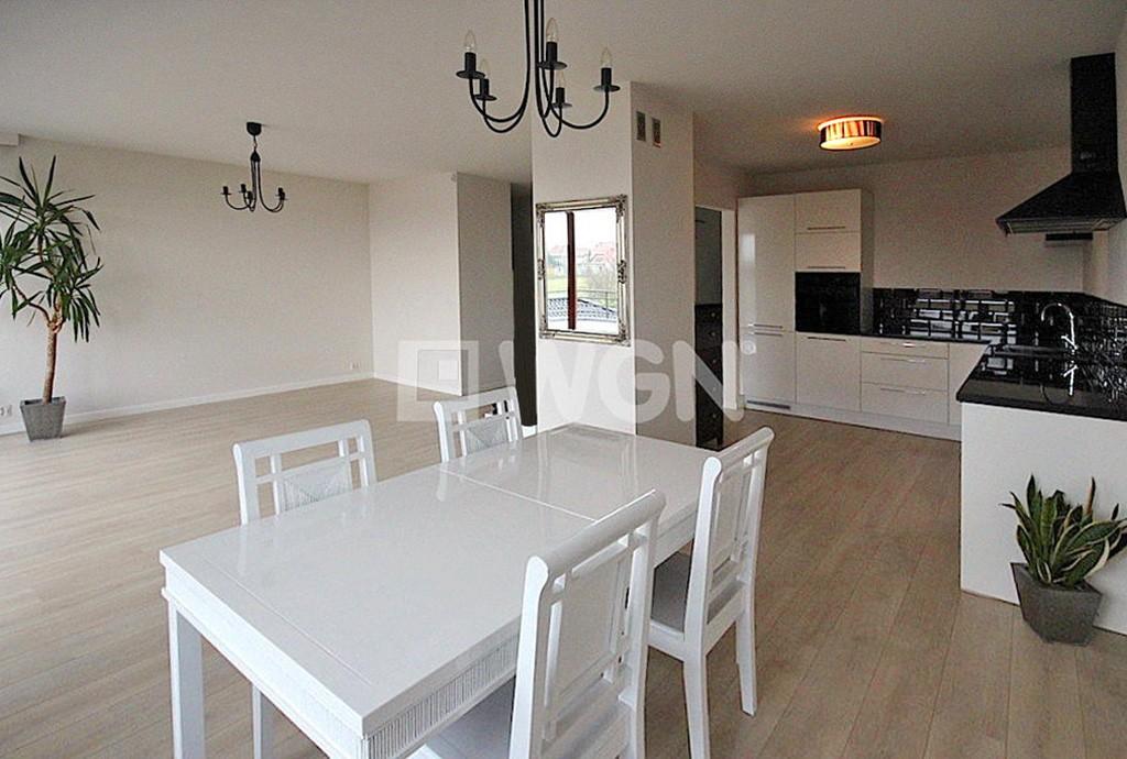 na zdjęciu widok od strony jadalni na fragment salonu i aneks kuchenny w apartamencie do wynajęcia w Szczecinie