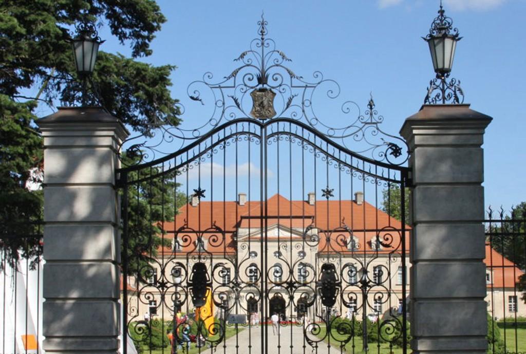 na zdjęciu front pałacu za reprezentacyjną bramą wjazdową w województwie wielkopolskim do sprzedaży