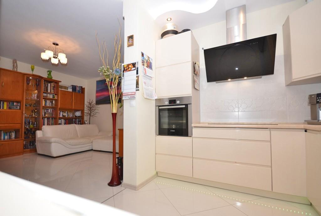 na zdjęciu aneks kuchenny oraz salon na drugim planie w apartamencie do sprzedaży w Warszawie