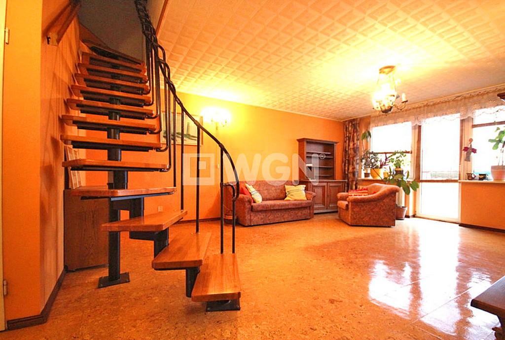 zdjęcie prezentuje salon oraz schody na drugi poziom w apartamencie do sprzedaży w Szczecinie