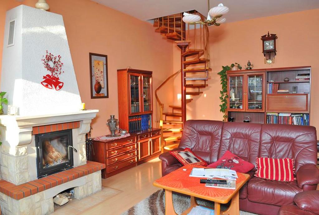 zdjęcie prezentuje na pierwszym planie kominek w salonie luksusowego apartamentu na sprzedaż w Szczecinie