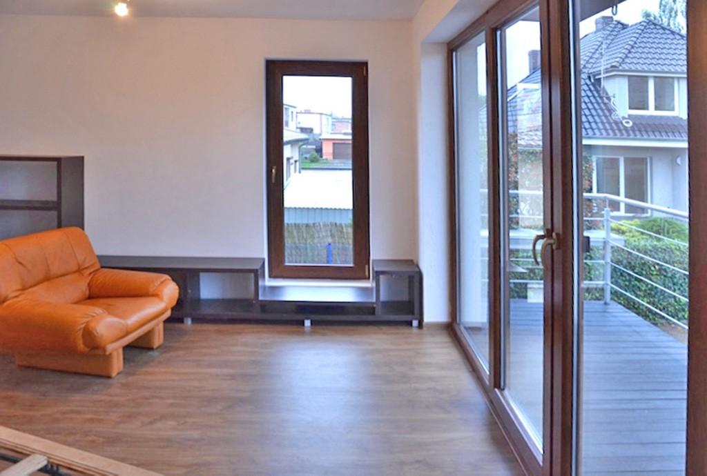 zdjęcie prezentuje fragment salonu z wyjściem na taras w luksusowym apartamencie do sprzedaży w Lesznie