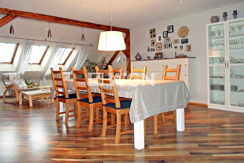 na pierwszym planie jadalnia, w oddali kuchnia w ekskluzywnym apartamencie do sprzedaży w Legnicy