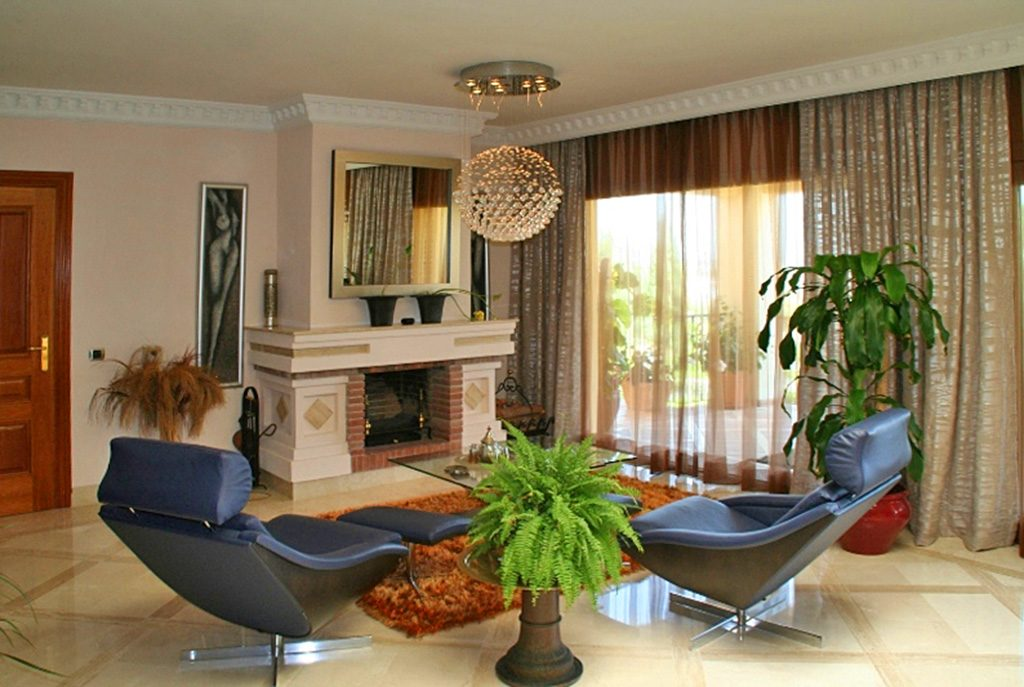 stylowy salon z kominkiem w ekskluzywnej willi do sprzedaży w Hiszpanii (Costa del Sol, Malaga)
