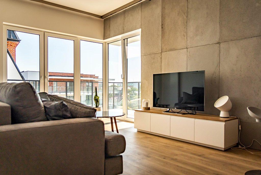 widok na salon oraz taras przy luksusowym apartamencie do wynajmu w Wieluniu