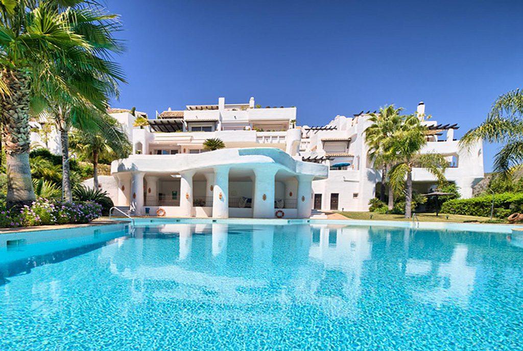 widok od strony basenu na ekskluzywny budynek, w którym znajduje się oferowany do sprzedaży luksusowy apartament Hiszpania (Costa del Sol, Marbella)