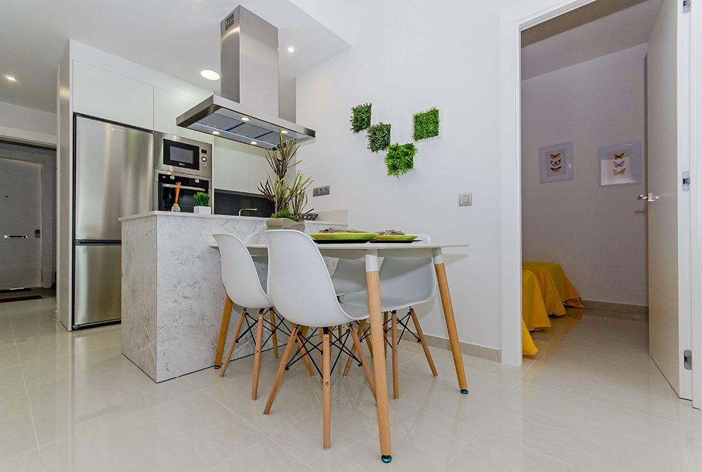 minimalistyczny wystrój jadalni i aneksu kuchennego w ekskluzywnym apartamencie do sprzedaży Hiszpania (Torreviej)