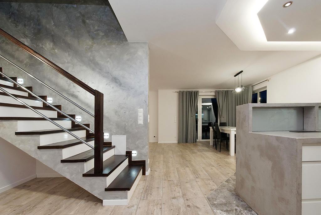 po lewej schody na górny poziom, po prawej aneks kuchenny w luksusowej willi na sprzedaż Tarów (okolice)