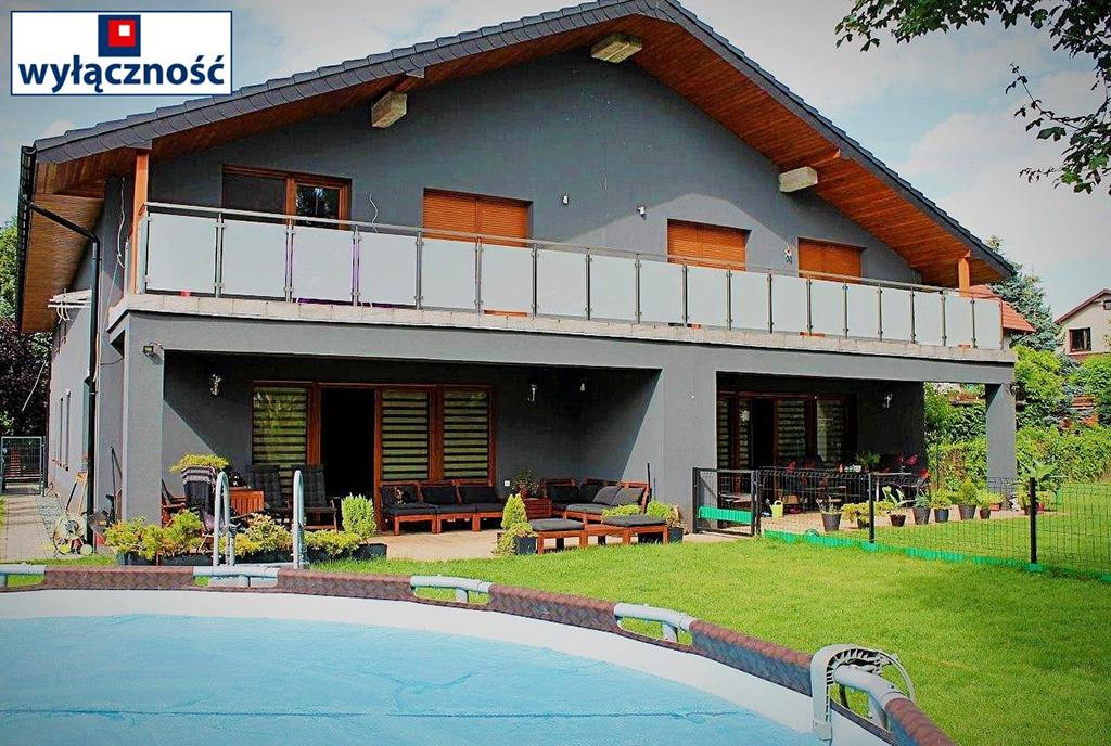 zdjęcie wykonano od strony basenu prezentujące okazałą bryłę luksusowej willi na sprzedaż Wrocław